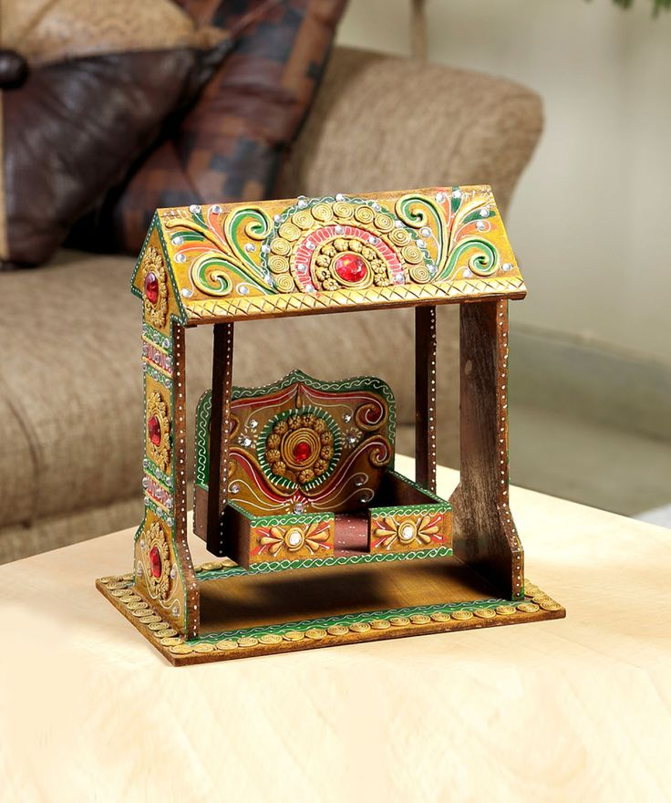 A sweet looking Jhula that has been crafted with solid wood and hand painted in a golden brown enamel and accents of green and red. with a delicate hand crafted clay work and kundans give a very ethnic appeal to this piece of décor. The art is intricate Mehendi like work where clay is applied delicately on wood just like Mehendi is applied neatly on hands with all concentration and dedication.fashionandyou.com brings to you artefacts from Aapno Rajasthan that shall leave you within a mirage…