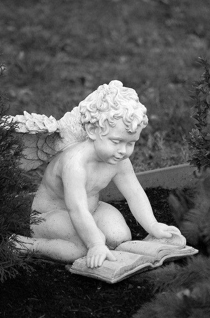 Escultura sedente realizada en piedra blanca. Posee una textura lisa y un acabado pulido. El significado es la ingenuidad que tienen los niños de pequeños que es también un tópico hoy en día, ejemplo de esto es el típico tu niño es un angelito. Además aparece leyendo como un buen niño, lo que le aporta más claridad al significado.