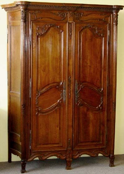 French, Neoclassical, period armoire de chasse: A very unusual form, most likely from a hunting lodge in Southwestern France.   In solid, carved cherry with additional storage cabinets on either side (see photo number three), which were used to store hunting gear.  Late 18th century.