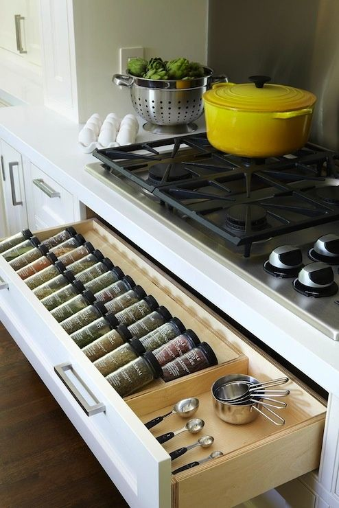 Kitchen with spice rack drawer below gas cooktop. Well organized pull-out spice drawer.