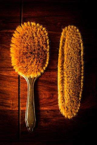 Stock image of 'A pair of vintage hairbrushes on solid dark wood'