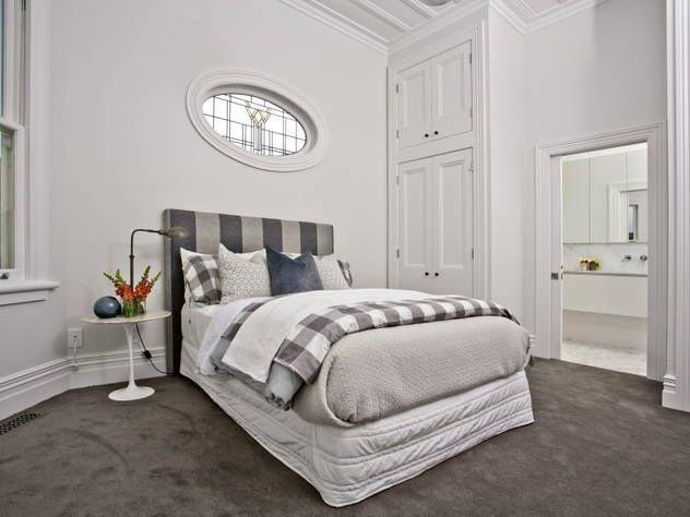 Bedroom of remodelled 3 bedroom c.1915 villa @ Oxford Terrace, Cheltenham. Dark grey carpeting, white painted walls and wood ceiling. Lovely leadlight window. (in Oct 2014)