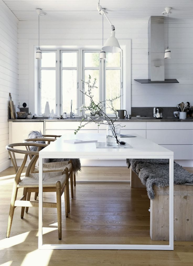 white kitchen with wooden floors and chairs | modern table with vintage chairs and bench with grey sheepskin