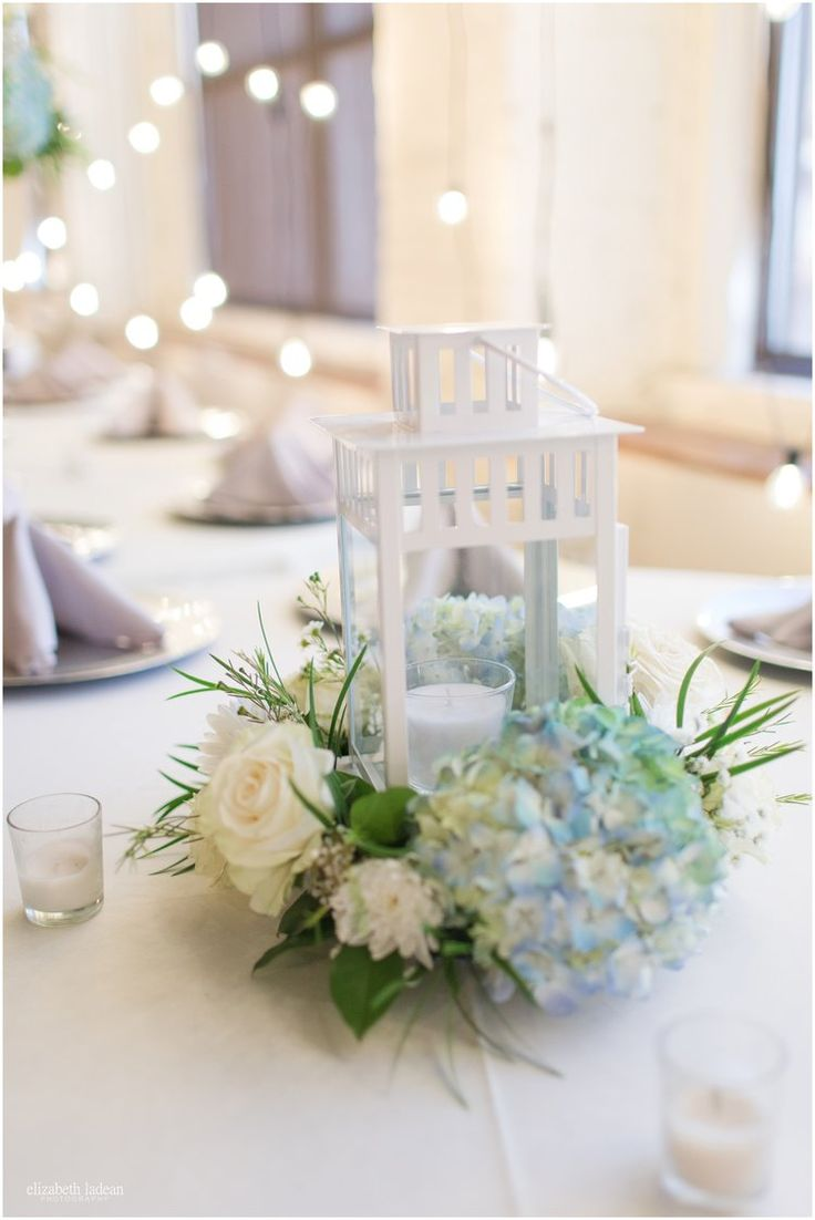 White lantern centerpieces with blue hydrangea with white flowers.
