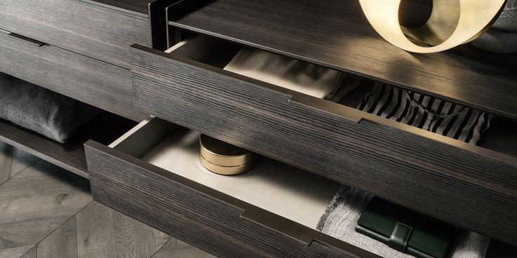 detail van het zwevende ladeblok met een bruine aluminium greep. De interne samenstelling van de lade is in grijs melamine in combinatie met een lederen afwerking.