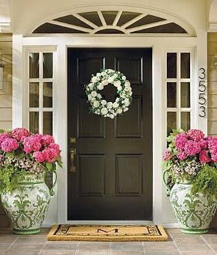 I'm in love with this entryway and the transom windows and arch with the grille patterns. Paint color is perfect for house, trim, and door. Not sure about the design on those pots, but the flowers are pretty. - AG