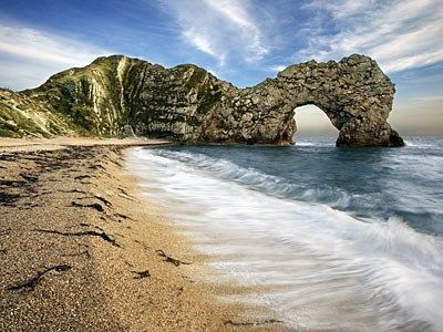 The view along a shingle beach to Durdle Door on the southern coast of England, United Kingdom. This is known as the Jurassic Coast, extending along the coastal counties from Devon to Dorset. 185 million years of fossil and geological history in 95 miles of coastline. Breathtaking.