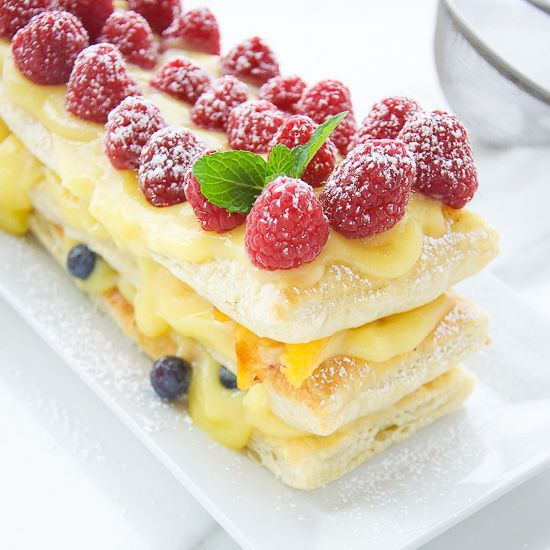 Berries And Peach Pudding Tart. Fresh blueberries, raspberries and peaches stacked in three layers with vanilla pudding and puff pastry.