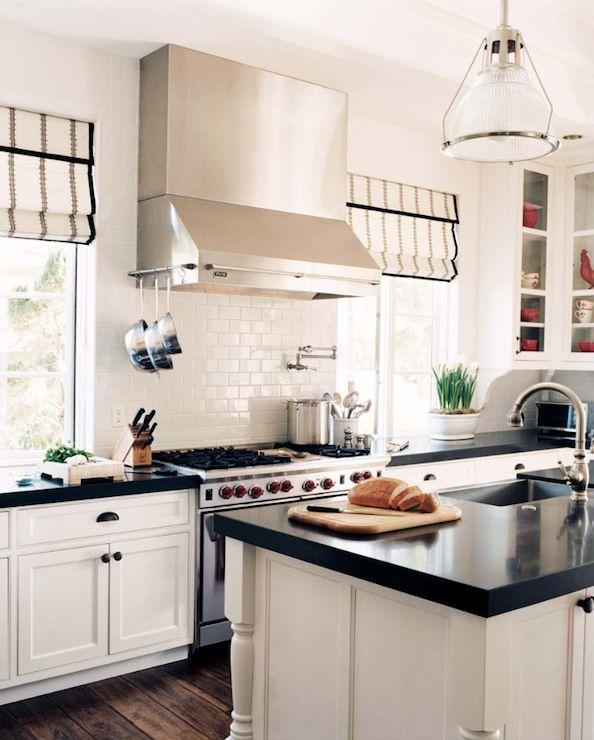 white kitchen, dark countertops, white subway tile backsplash, medium hue reclaimed barnwood floors