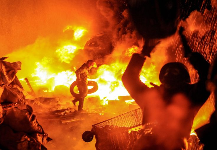 Protesters burn tires as they clash with riot police during an anti-government protest in downtown Kiev, Ukraine, Jan. 22. At least two people died of gunshot wounds on January 22 during anti-government protests in Ukraine. (ROMAN PILIPEY/EPA)