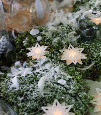 Lass dich von der Natur inspirieren. Wie wäre es z. B. mit einem verzauberten Winterwald auf dem Tisch?STRÅLA LED-Tischdekorationen in Sternform in Weiß auf grünem Moos auf einem Tisch