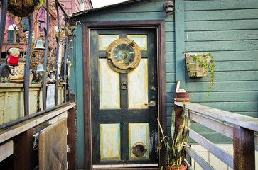 The decorative metal screen and porthole window in the door allude to the intriguing experience beyond. The porthole was found at The Seattle Antique Market.