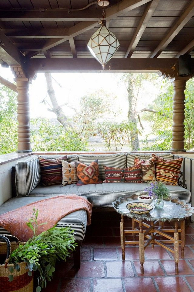 Bohemian inspired patio with a cozy bench and a Morrocean inspired pendant light