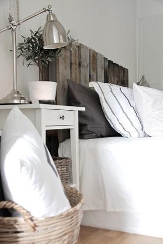 Sengegavl lavet af paller. Opsat på væggen.   Kurv til tæpper, puder og lign.