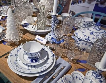 The Royal Porcelain Factory Table – Danish blue and white china in the Blue Fluted Plain, Mega and Half Lace patterns are mixed on a handmade wood table decorated with blue flowers.