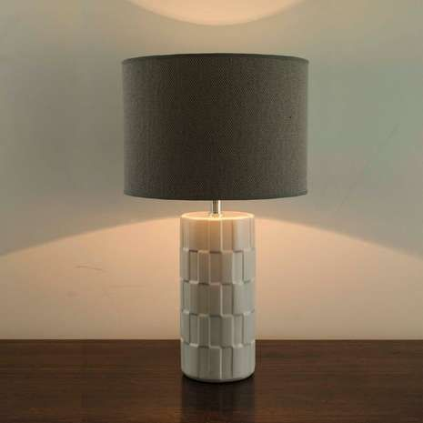 Crafted from ceramic, this white table lamp features an embossed base with geometric patterns and is completed with a grey linen lampshade....
