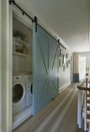 Repurposed barn door serves as a laundry closet slider
