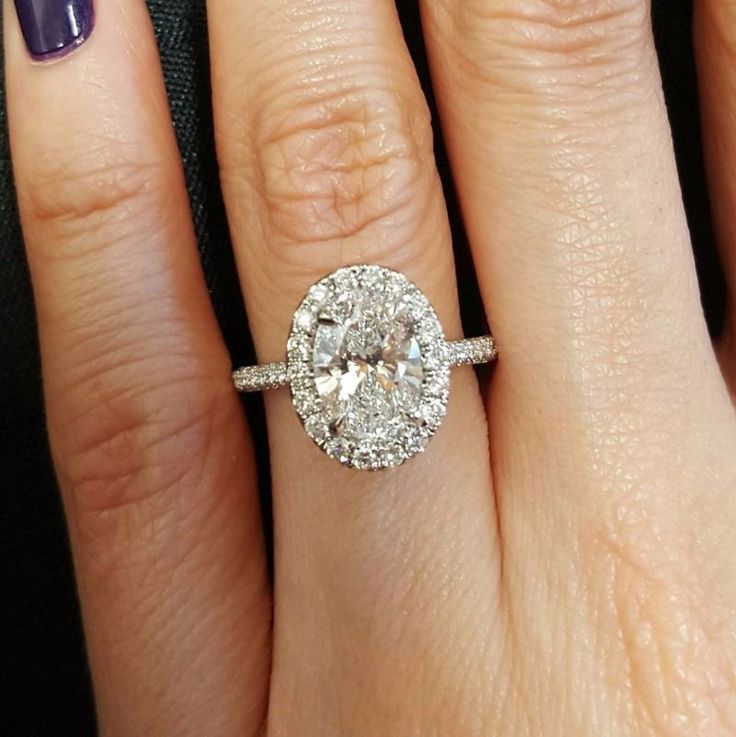 This oval shaped diamond halo engagement ring is stunning and so flattering on the finger. | mysweetengagement.com