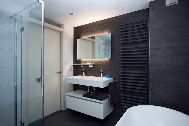 Deze modern ingerichte badkamer voldoet aan alle eisen. Een ruime douchecabine voor als het snel moet en een modern ligbad om heerlijk in weg te dromen.
