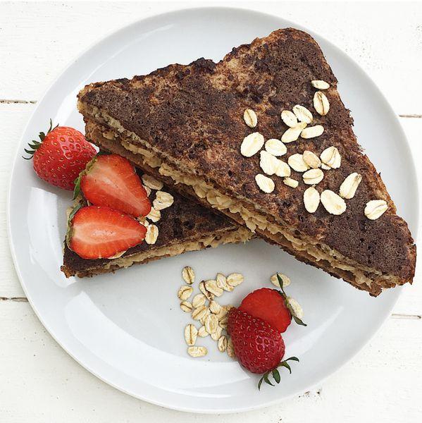French toast light al cacao con albume ripieni di porridge al burro d'arachidi con banana e fragole. Per una colazione nutriente e sana.