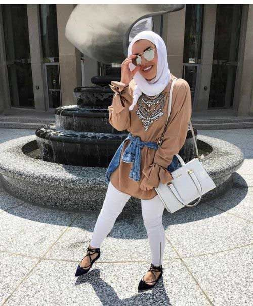 Tan top with statement necklace, white jeans, hijab and bag and black lace up flats.