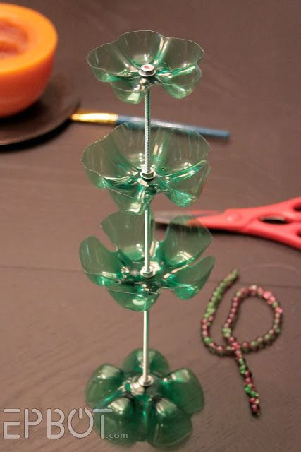 """Two 2-liter, one 1-liter, and one 20-oz bottles, 12-inch length of threaded rod, coordinating size nuts and washers. Drill holes same size as threaded rod in center of each tray. For bracelet hanger, cut between the """"petals"""" of the last bottle bottom to separate them. Cut as far down into  plastic as you can with scissors, use Dremel to smooth jagged bottom. Assemble stand. Sandwich each tray between two washers and two nuts. Glue glass bead to top nut."""