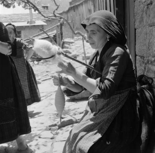 Greece, woman spinning fibers using distaff and drop spindle in Métsovon