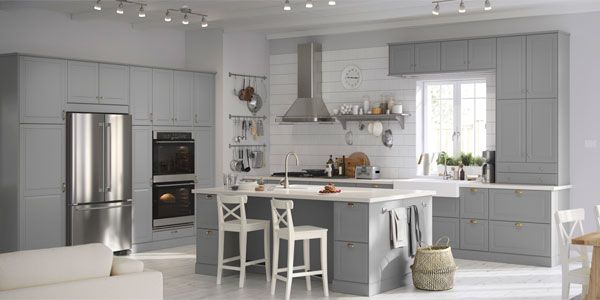 Bright IKEA kitchen with dark cabinets, stainless steel appliances and a white kitchen island.