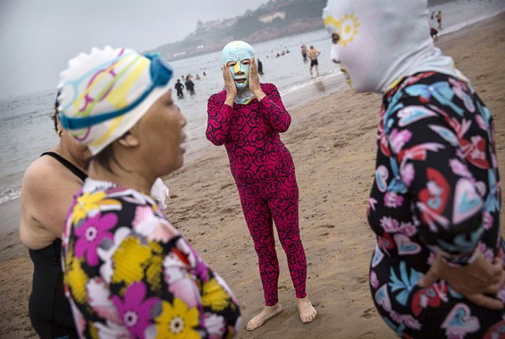 The seaside city of Qingdao in China's eastern Shandong province has made its mark in fashion history this month as photographs trended online of beachgoers wearing what has possibly become the latest, and unlikeliest, in swimwear couture: the 'face-kini' Picture: Kevin Frayer/Getty Images.  Qingdao locals enter fashion history as 'facekini' becomes an Internet   sensation
