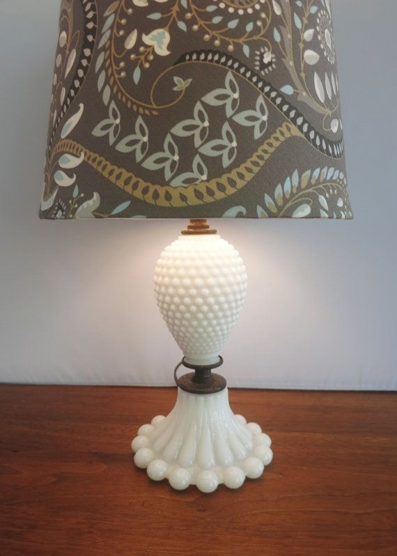 Charming vintage hobnail milk glass accent lamp with beaded base. Perfect for a desk, night stand, end table or vanity. Perfect for adding a farmhouse or cottage chic touch to your home. Its in great condition for its age and is in working order with the original cord. No chips or cracks. This listing is for the lamp only. Lamp shade not included.  Just under 11 tall and base is 5 in diameter.  **Lamp only, lamp shade not included.  *** As with all vintage electronics, I cannot guarantee…