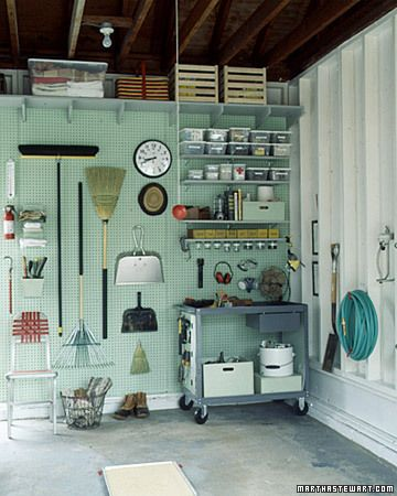 AWESOME!! Pegboard Organizer  A pegboard organizes tools and brooms, while a metal cart serves as a mobile workbench. Adjustable shelves display an assortment of containers, including a painted wooden box that stores glue; glass jars contain small hardware. And the pan of sand on the floor catches oil drips from the car.