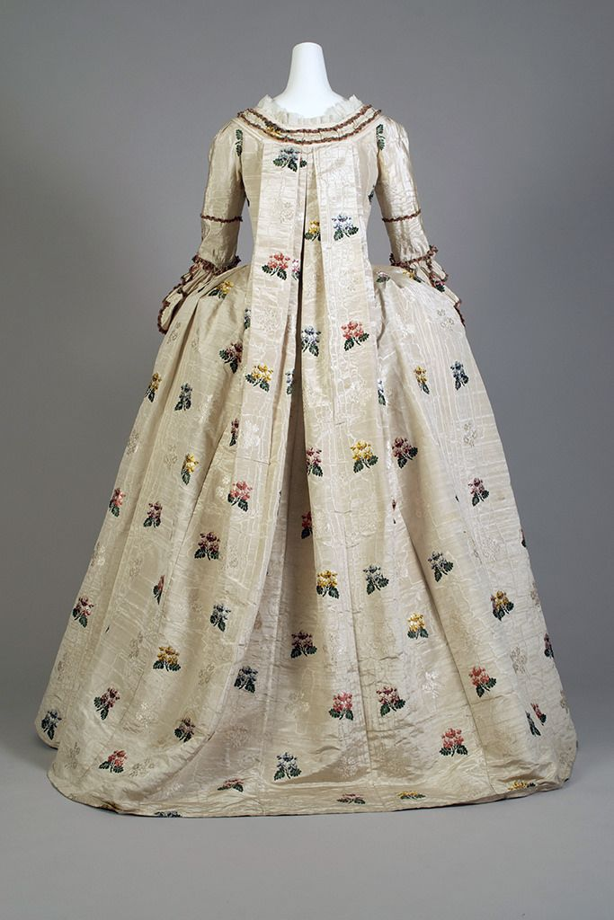 Robe à la française, ca. 1748-1752 | Dress, petticoat, stomacher. White moire brocaded with red, purple, yellow and blue sprays. Skirt: Hem ruffle, trimmed with chenille. Dress: fitted, full skirt, self robings, chenille trim. Stomacher: matching. Seperate pocket on a string with matching fabric. English, ca. 1748-1752. Silverman/Rodgers Collection, KSUM 1983.1.24.