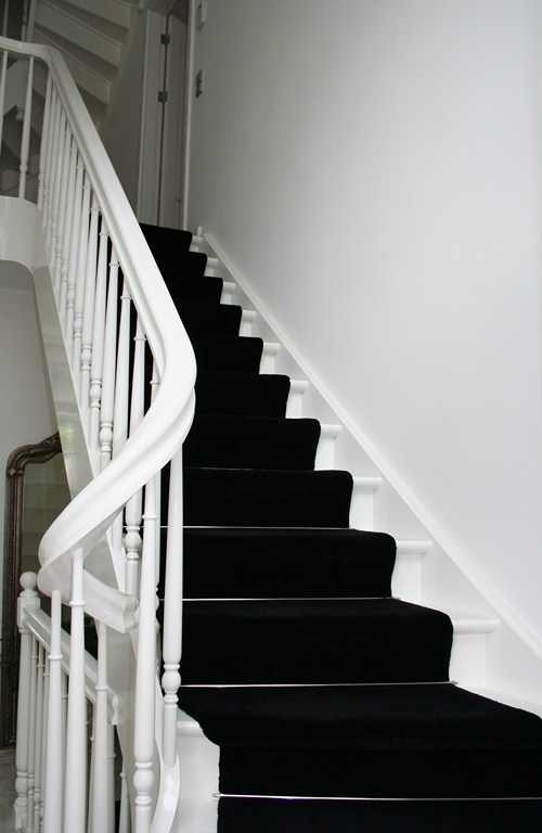 White stairs with black runner.