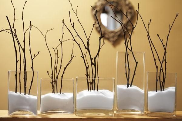 Create a beautiful winterscape by adding salt, to resemble snow, into clear glass containers and inserting sticks. Place the display on a fireplace mantle or ledge with overhead lighting to bring out the shadows on the top surface of the salt.