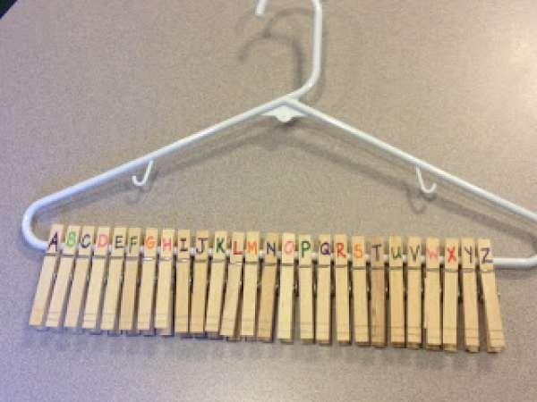 Apprendre l'alphabet en rangeant les pinces à linge sur un cintre par ordre alphabétique. 14 activités pour apprendre aux enfants à écrire en s'amusant