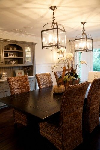 Dining room: Wayne's Coating; Farmhouse wood table; gray console, outdoor/indoor lanterns; dark hardwood floors; chairs in yellow/tan damask floral and basic tan or wicker/rattan