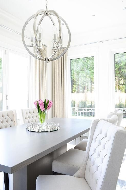 Chic dining room features a gray pedestal dining table lined with white wingback dining chairs ...
