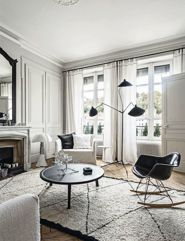 In this beautiful Paris apartment from Looks Like White, a black chair, a modern black lamp and a bold coffee table offer shadows of contrast for the mostly-white room.