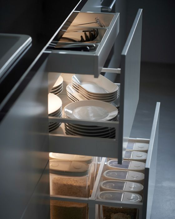 A close-up of three well-lit kitchen drawers are pulled out.