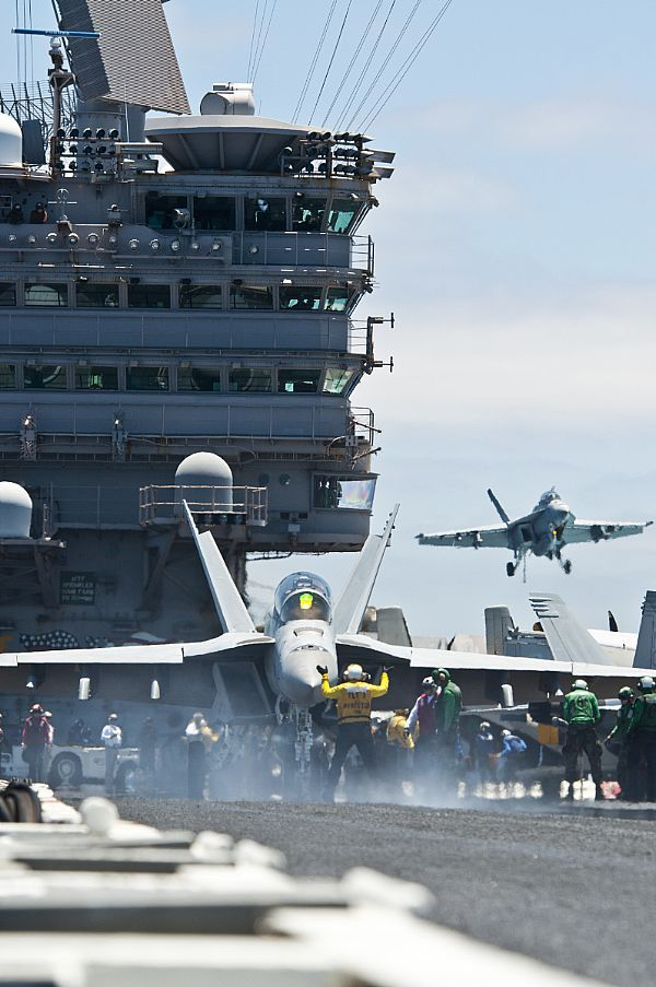 An F/A-18F Super Hornet from the Black Aces of Strike Fighter Squadron (VFA) 41 is directed onto the catapult on the flight deck of the Nimitz-class aircraft carrier USS John C. Stennis (CVN 74).