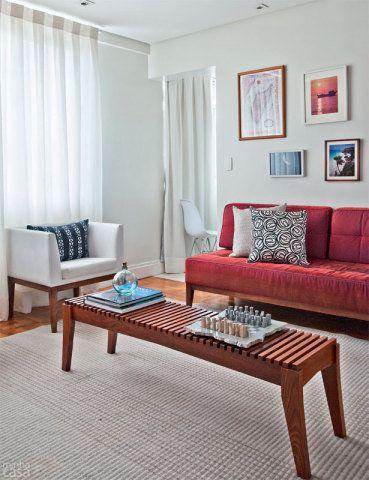 O tapete indiano demarca o território do estar: ao avançar sob os pés dianteiros das poltronas e do sofá, garante elegância à  composição. A parede atrás do sofá reúne os quadros de modo harmonioso, porém livre de regras. Projeto da designer Patrícia Ribeiro.