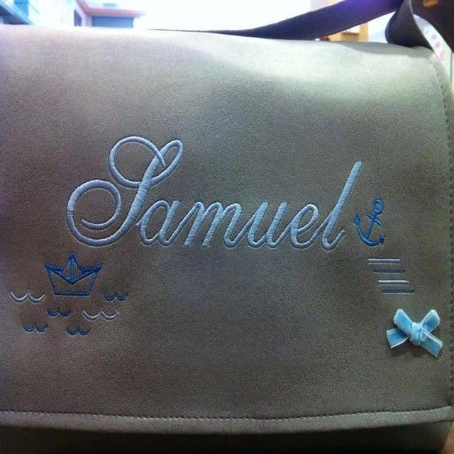 Bolso polipiel tapas de color gris con bordado completo de color azul marino y azul claro.