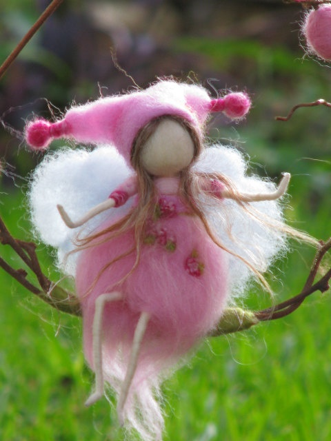 felted fairy sitting on a twig