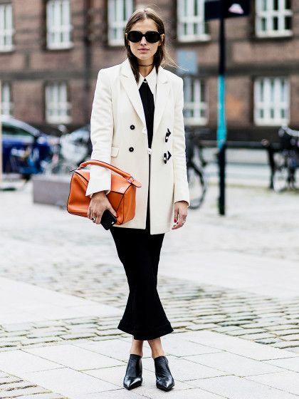 Fashion Editor Darja Barannik in einem cremefarbenen Longblazer und schwarzen Kick Flare-Pants mitorangefarbener Loewe-Tasche