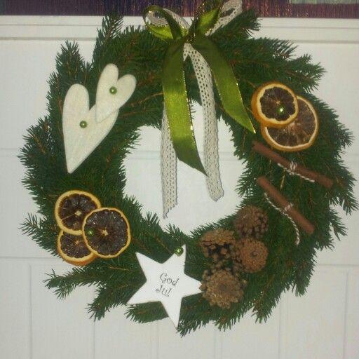 Granriskrans pyntad med tallkottar, filthjärtan, kanelstänger,  torkade apelsinskivor, pärlnålar och vackra band.