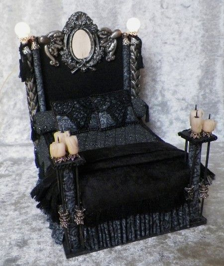 Gothic design Double size bed. Handmade appliques, heavy olde world influence. Castle & dragon stuff! Candles at the foot, fancy bed posts and two working lamps at the head..Dressed in black and grays, with velvet fringed blanket. Truly an masculine, masterpiece for the period...$169 www.ruthellens.fa...