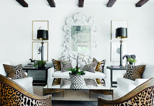 A Chic Austin Retreat          {The dramatic living room features wooden beams, slipcovered furniture in pure white, Scalamandré leopard print fabric on pillows and a pair of gilded chairs, and a play on scale via the tall table lamps and beautiful antiqued mirror.}