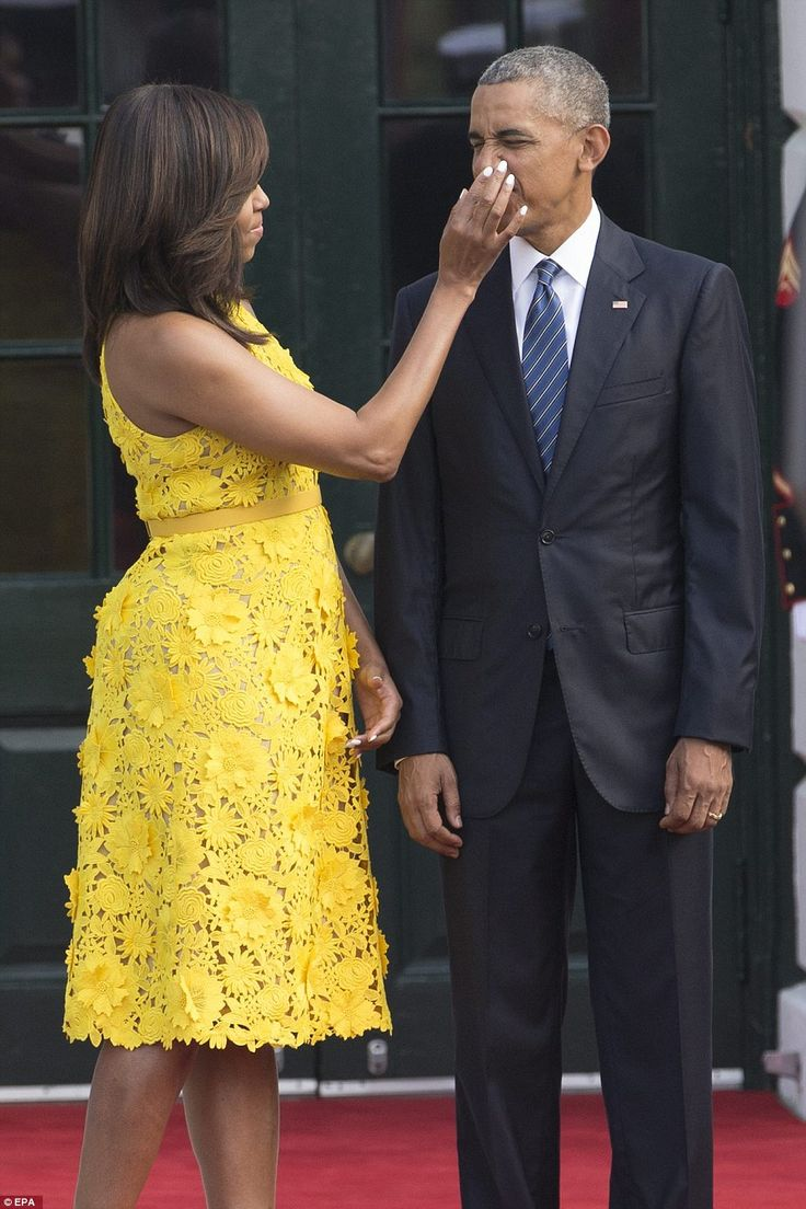 Michelle Obama wipes something off the president's nose as they prepare to welcome the Pri...