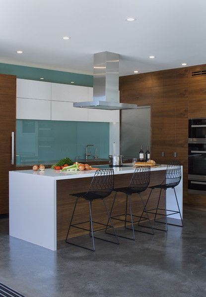 In the kitchen, a blue glass backsplash evokes the designers' native Iceland. The <br>Bend Goods stools are from YLiving.