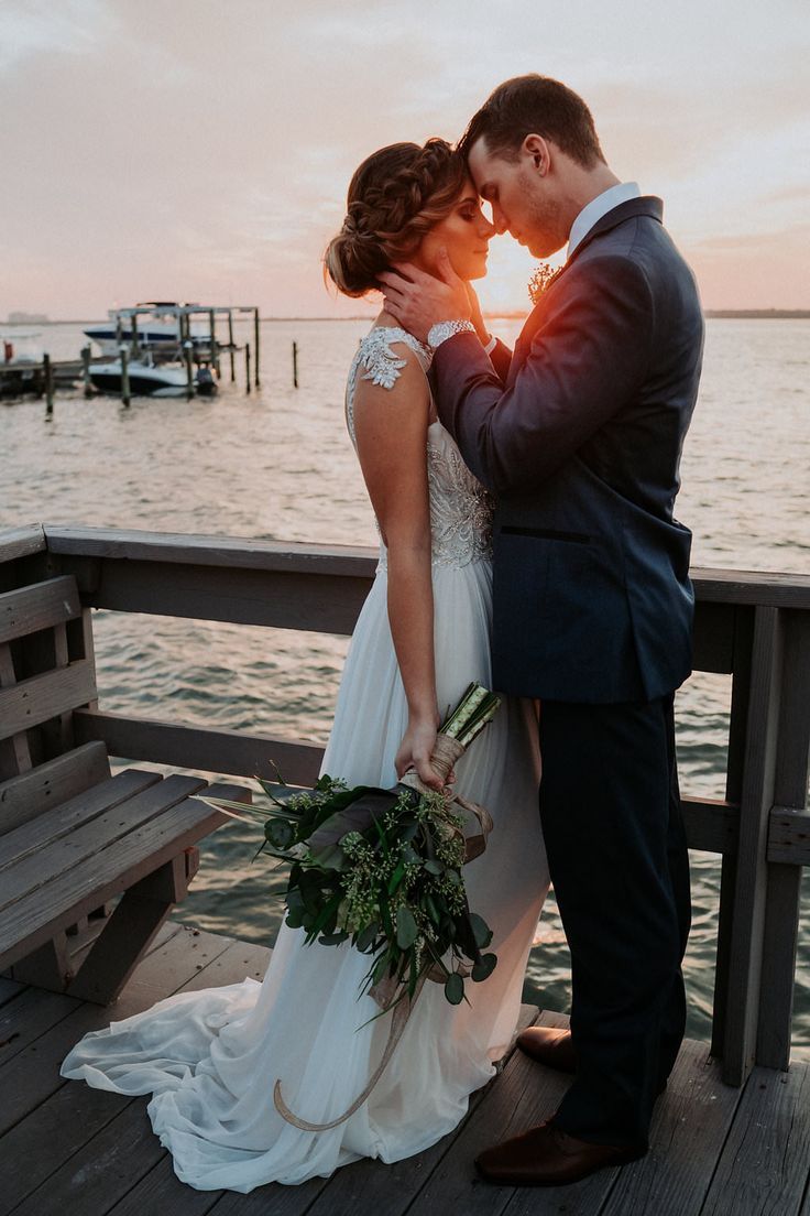 Outdoor Sunset Portrait on Waterfront Dock, Bride wearing Jeweled Lace Drop Back A Line Wedding Dress, Groom in Navy Suit with Silver Vest from Tampa Bay Formalwear Shop Nikki's Glitz and Glam | Dunedin, Florida Waterfront Wedding Venue Beso Del Sol Resort | Tampa Bay Wedding Photographer Grind and Press Photography